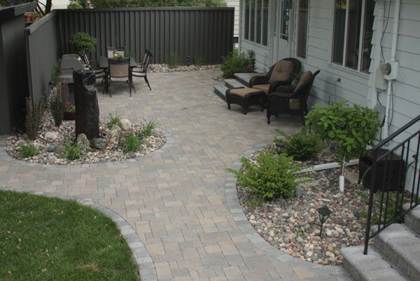 Willow Creek's weathered Cobblestone pavers in Lakeshore Blend with a border course in a contrasting charcoal to create a sweeping, curving patio for entertaining plus a walkway to a storage shed