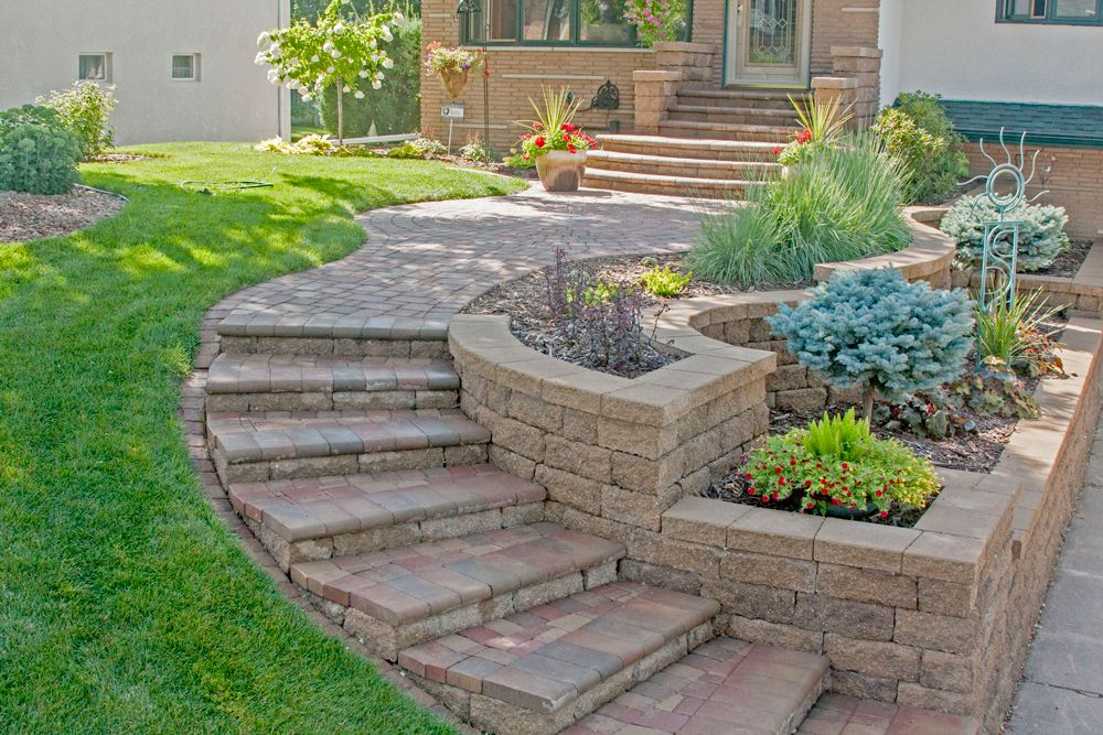 The curved walkway and staircase give the home great curb appeal and a graceful transition of the slope to the driveway. Planters created with VERSA-LOK retaining wall blocks add interest with curves, corners and stepped appearance as well as ample planting space for a bounty of plants and shrubs.