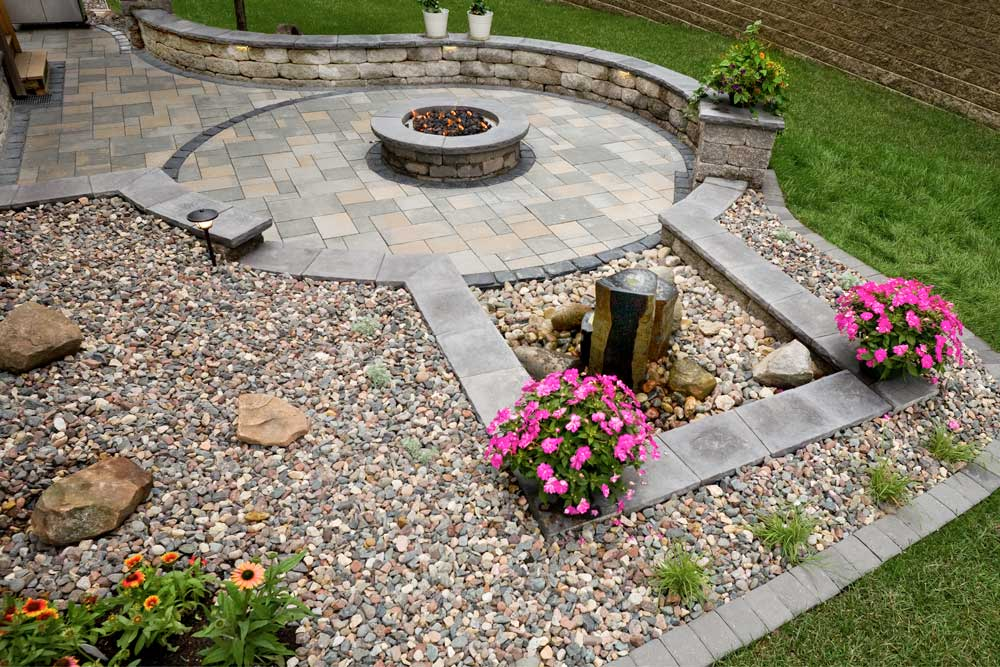 This backyard landscape design includes a fire pit and a water feature plus outdoor seating.