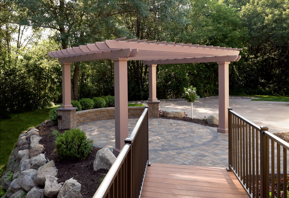Boulder retaining wall and paver patio with pergola.