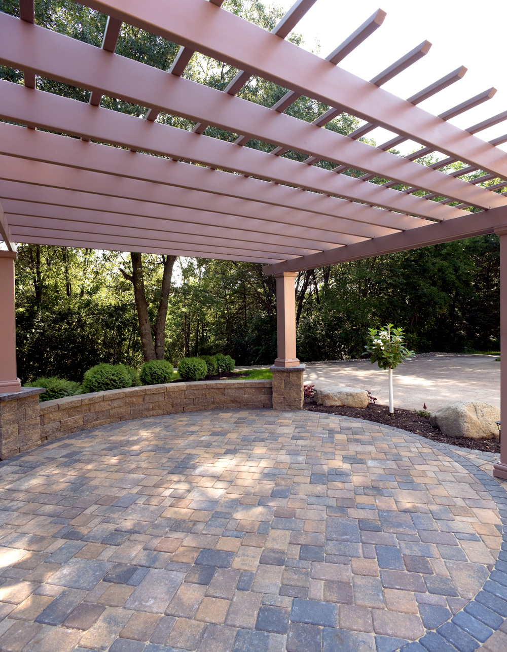 This circular paver patio is stunning with the colors and contrasting border course of pavers, planter walls, and natural boulders.
