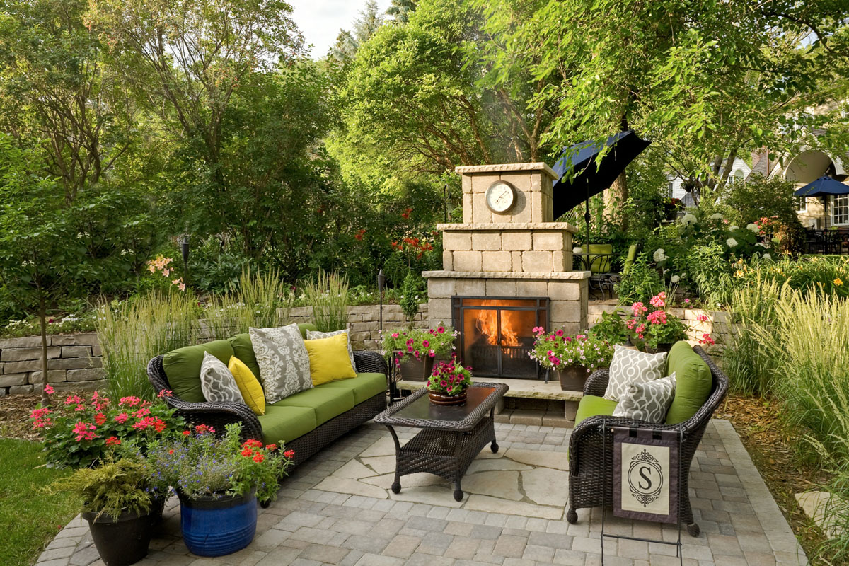 Gather around the outdoor fireplace in this beautiful patio design by Villa Landscapes.