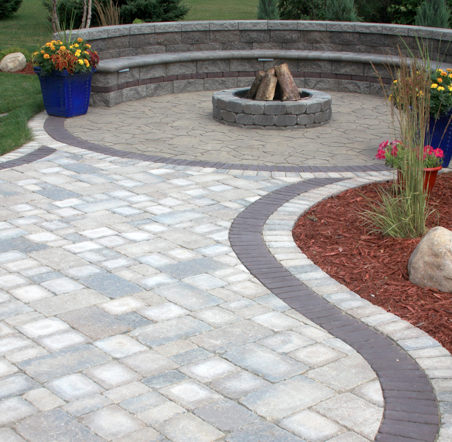 A paving stone walkway leads to a fire pit and circular paver patio with outdoor seating.